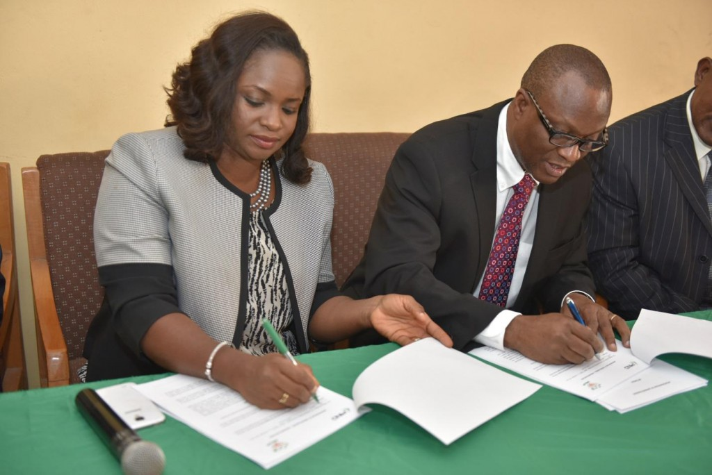 PIND Program Director Dr. Dara Akala and Ondo State WECA Chairperson Bolanle Olafunmiloye sign the paperwork